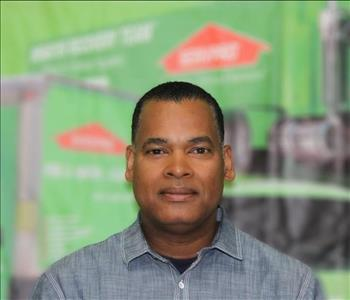 a man in a collared shirt in front of a green background
