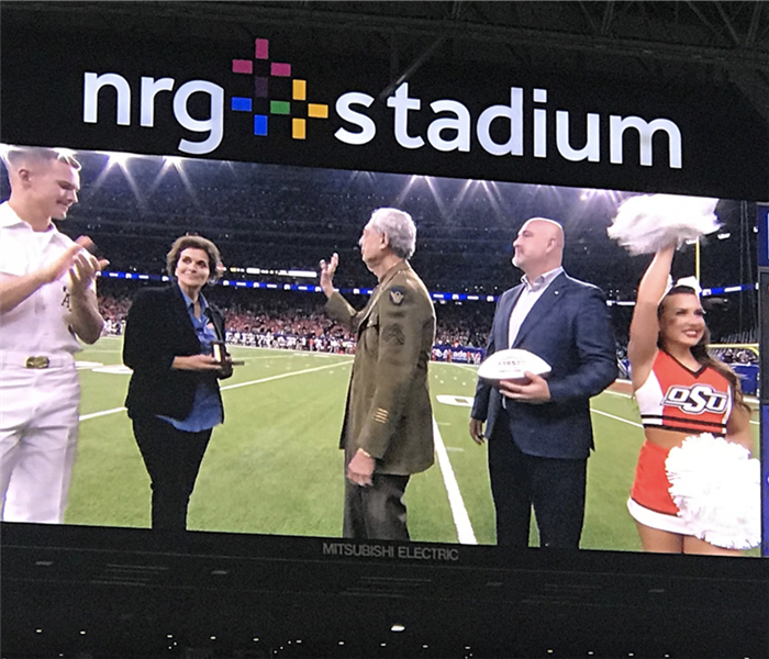 Five people waving to a stadium audience.