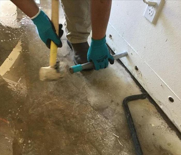 water on the floor of a property, a man making holes in sheetrock to aid in drying process