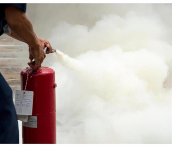A man practices how to use a fire-extinguisher