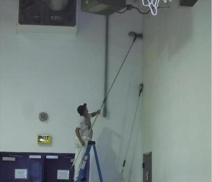 worker cleaning soot damage in a school