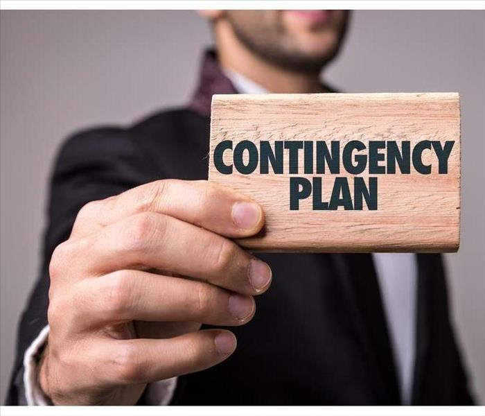 "A man holding a piece of wood with the word ""contingency plan"" on it"